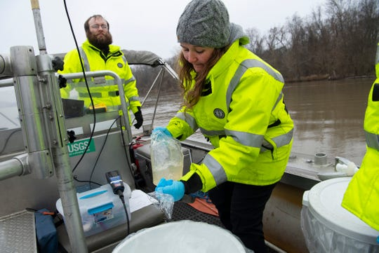 U.S. Geological Survey hydrologic technician Molly Lott, right, pours a water sample into a collection bucket as Nathan Truax keeps their boat on course while on the Wabash River in New Harmony, Ind., Monday morning, Jan. 27, 2020.