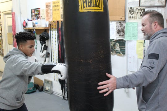 Elijah Karlovetz, left, takes swings at heaving back as Fremont Wreckers Boxing Club coach Joe Laughlin shouts instructions.
