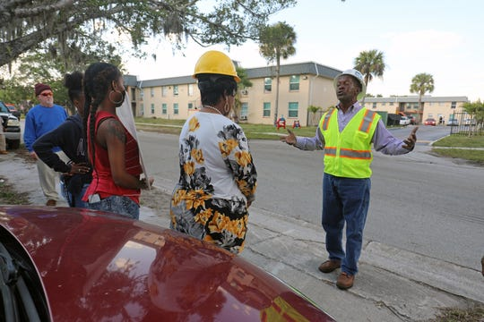 Lee County NAACP President James Muwwakil talks to arriving demonstrators outside the Royal Palm Apartments (formerly Jones Walker) in Fort Myers on Tuesday afternoon.  It is the second demonstration in a week seeking local labor participation in a major construction project that will rehab the 80-unit complex top to bottom.