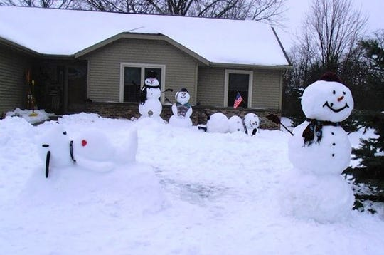 """Linda and Dennis Hemauer used recent snowfall to add some fun to their front yard in the 1200 block of South Park Avenue. The couple built multiple snow sculptures, including Snoopy, and a child snowman getting a ride on the """"shoulders"""" of another snowman."""