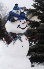 """This year's snowman display by the Hemauers had a new addition thanks to some Pinterest inspiration: an adult snowman giving a child snowman a ride on its """"shoulders."""""""