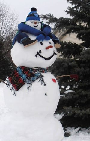"This year's snowman display by the Hemauers had a new addition thanks to some Pinterest inspiration: an adult snowman giving a child snowman a ride on its ""shoulders."""
