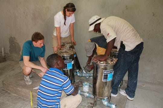 """Clemson Engineers for Developing Countries participants (left) help install a water pump in the Cange region of Haiti. Clemson students involved with CEDC said they gain valuable job and global thinking skills through the program, which are key goals in the College of Engineering, Computing and Applied Sciences """"Grand Challenges"""" curriculum."""