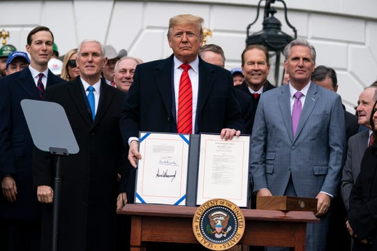 President Donald Trump shows off a new North American trade agreement with Canada and Mexico, during an event at the White House, Wednesday in Washington.