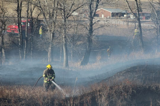 A volunteer firefighter douses the flames of a grass fire that burned northwest of Vaughn on Wednesday