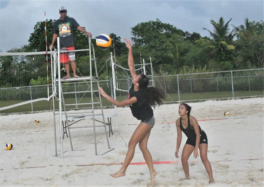 St. John's Yasmeen Lopez takes a set from Nikki Mathews and  rips a shot against Academy during their IIAAG Girls Beach Volleyball match Jan. 28 at the Guam Football Association National Training Center's sand courts.