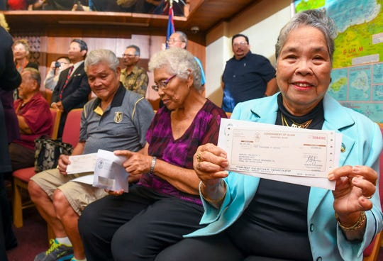 War claims recipient Felicita Naputi, front, happily displays a check she received from Gov. Lou Leon Guerrero during a presentation at Adelup Jan. 29. Naputi and 13 other claimants were the first to receive the long awaited funds during the brief ceremony.