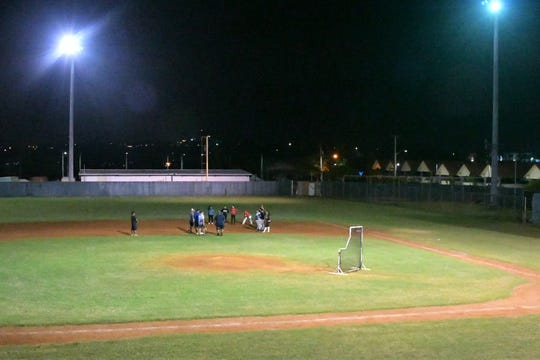 Three times a week for at least two hours each day, the Guam Women's National Baseball Team  comes to practice and works hard. They are shown here under the waning lights Jan. 23 at the Paseo Stadium
