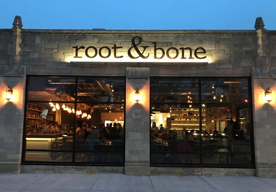 At twilight, under a deep-azure sky, lanterns and backlights illuminate buff stonework framing the warm, golden bustle of diners inside Root & Bone. The restaurant opened in January 2020 at 4601 N. College Ave., south of Broad Ripple in Indianapolis.