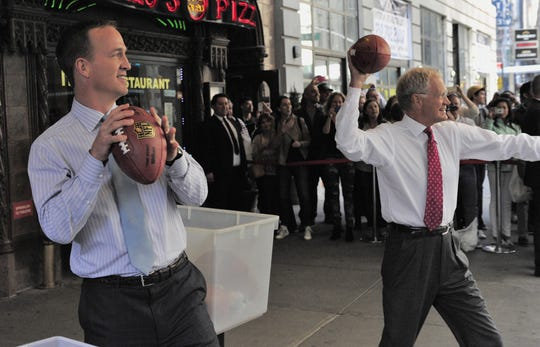"Peyton Manning and Late Show host David Letterman try their passing skills at moving New York City cabs with open windows during a May 5, 2014, taping of the ""Late Show"" New York."