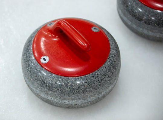 One of the curling stones on the ice during league play with Circle City Curling Club, at Fuel Tank at Fishers, Friday, Jan. 24, 2020. Each of these stones has a handle affixed to it that allows the granite below it to be rotated during a throw.