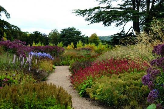 """In the long borders he designed to flank a pathway at the Trentham Estate in England, Oudolf punctuated the landscape with several clumps of identical grasses. """"Repeating plants at regular intervals adds rhythm and variation,"""" says Oudolf. """"It creates a feeling that 'this is one place, with one design and one vision.'"""""""