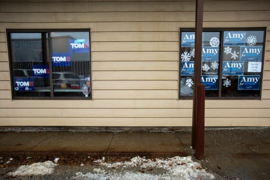 Window signs hang at an office for Democratic presidential candidate Tom Steyer, Thursday, Jan. 23, 2020, next door to a field office for Democratic presidential candidate U.S. Sen. Amy Klobuchar, D-Minn., in Iowa City, Iowa.
