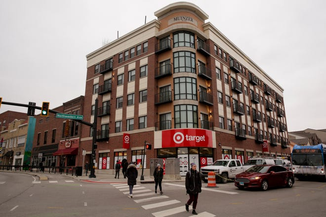 """Pedestrians walk by the Muinzer Building at the corner of State Street and Northwestern Aveune, Wednesday, Jan. 29, 2020, in West Lafayette. On the ground floor, a Target store displays a """"we're hiring"""" sign."""