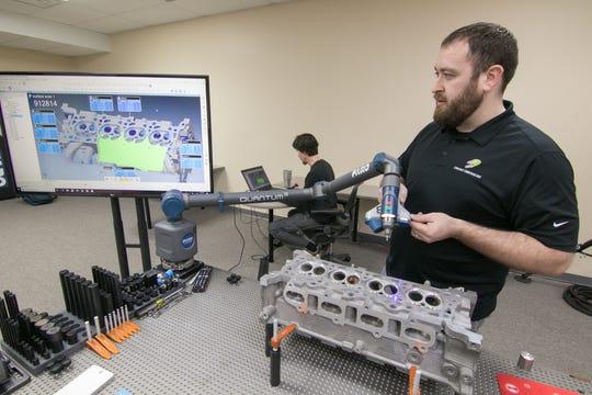 Diverse Dimensions metrologists Derek Beebe (foreground) and Tim Benjamin scan and analyze the surface of a car engine's cylinder head at the company's new Brighton Township facility Wednesday, Jan. 29, 2020.