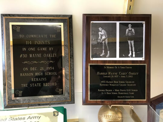 These plaques in the Hanson Elementary trophy case commemorate Wayne Oakley's record-setting 114 points in a high school basketball game.