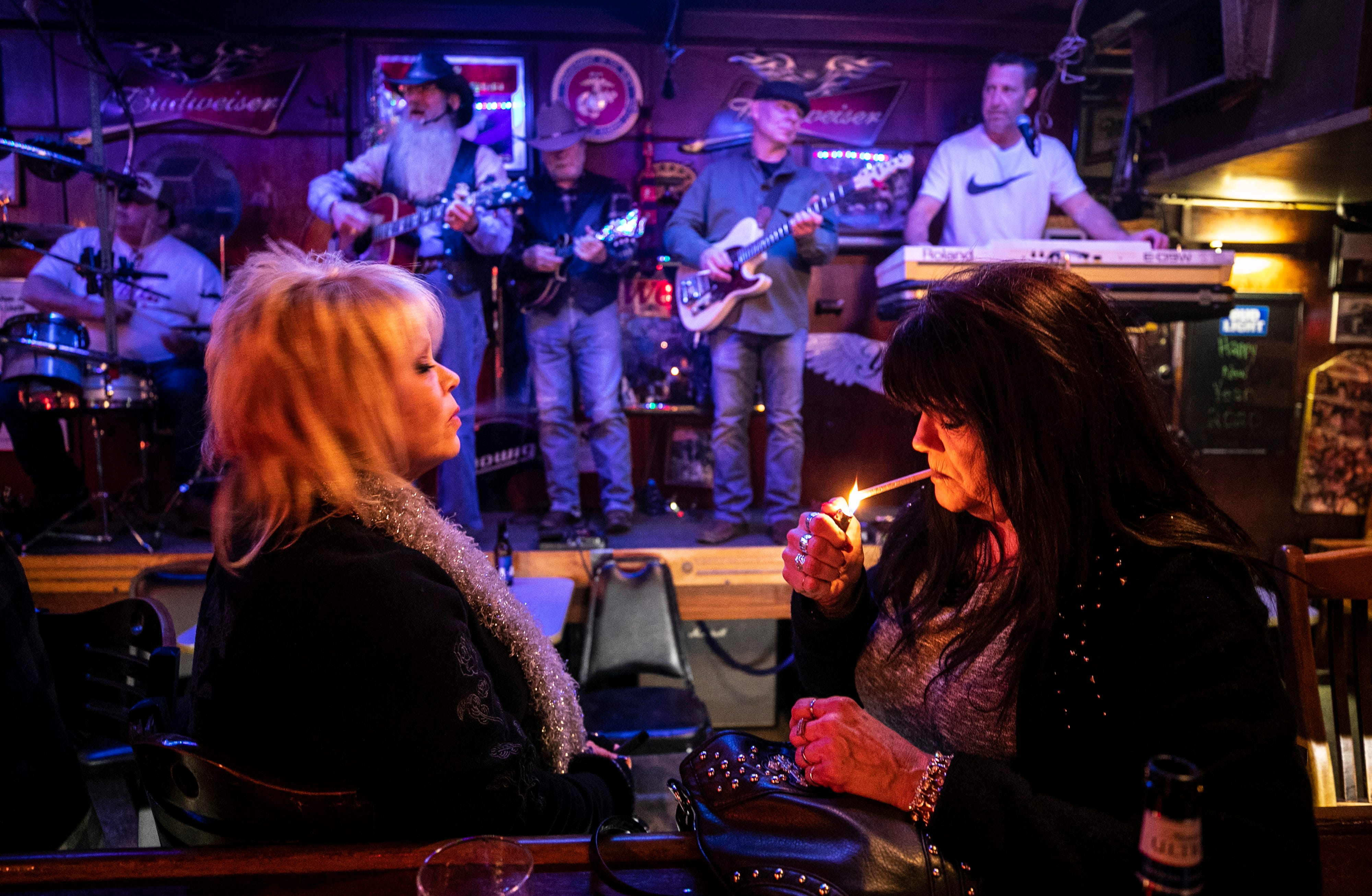 """11:20 PM   Bar patron Missy lights up a cigarette as friend Toni looks on as bar owner Hugh E. Bir — with the long white beard — plays with musician friends. Bir, 66, has owned the bar since 1966. Live music """"is my therapy,"""" said Bir, who performs three nights a week at the small New Albany bar."""