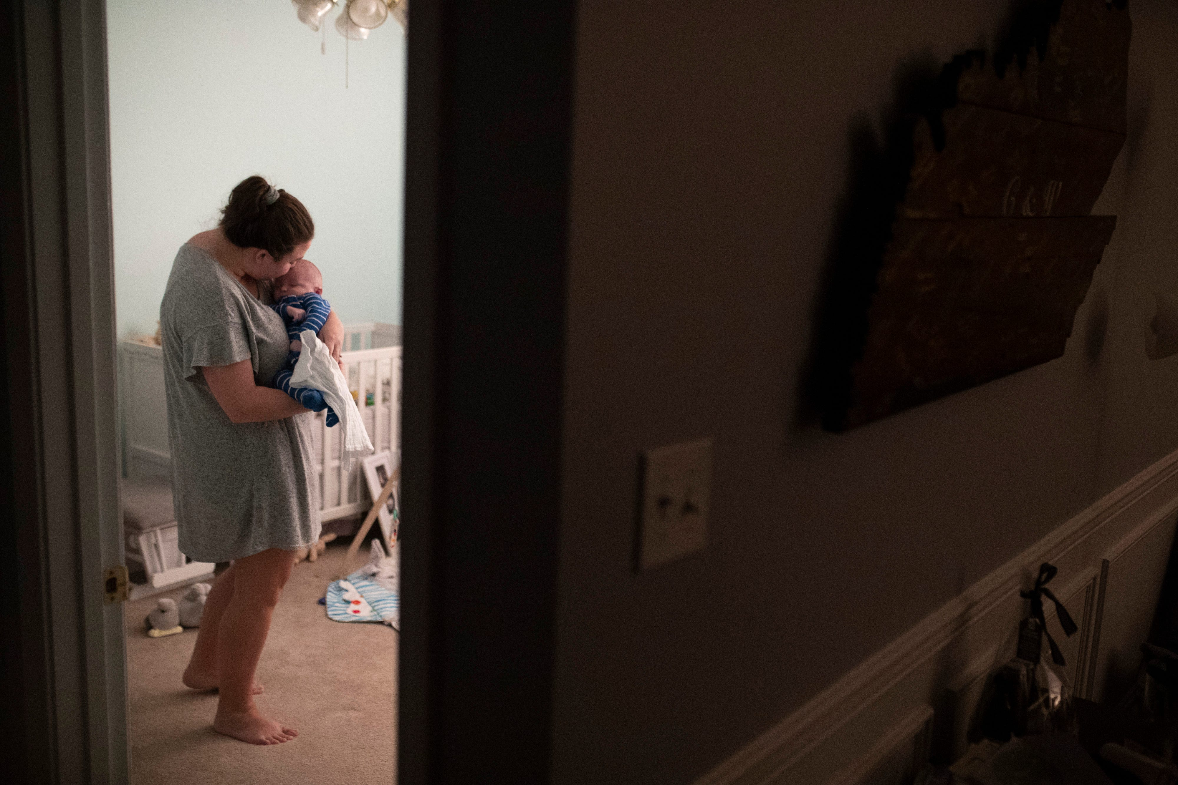 """2:34 AM  Christina Rose kisses her newborn Palmer, born Nov. 16, after waking up past midnight to calm his cries with some milk and rocking before putting the young boy back to bed on Jan. 24, 2020. """"He eats every three to four hours so that usually gets us up in the middle of the night,"""" Rose said. """"Being a new mom has been nothing that I expected. It has been the most challenging and rewarding thing at the same time."""" Jan. 24, 2020"""