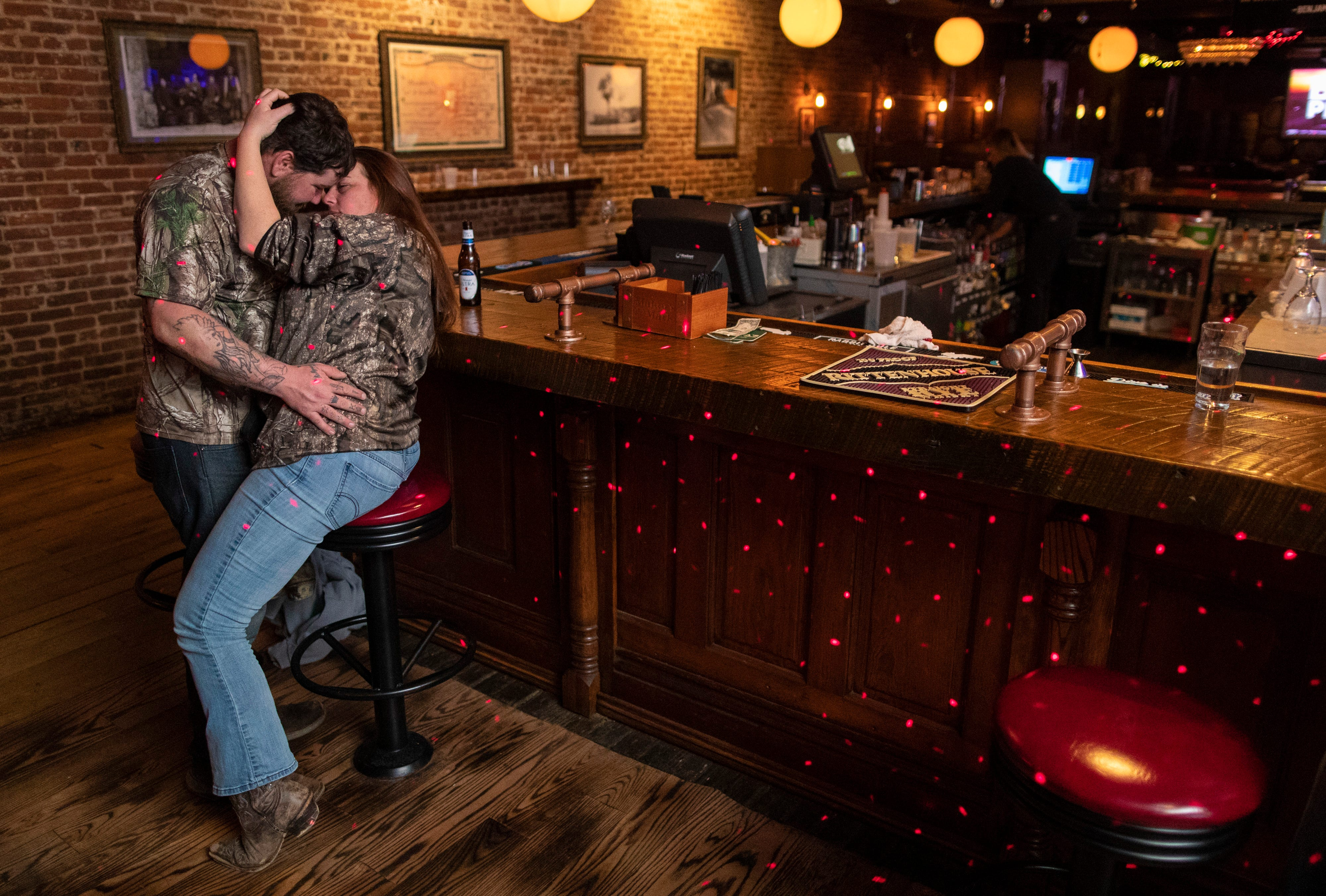 """Andrew Williams, left, and Amber Ritter pull each other close after a late night for karaoke at O'Shea's in downtown Louisville on Jan. 26, 2020. """"I've come to be good friends with DJ Michael Lawson,"""" Williams said. """"I stumbled in here one night and I heard some off-key music and I've been coming here ever since."""""""