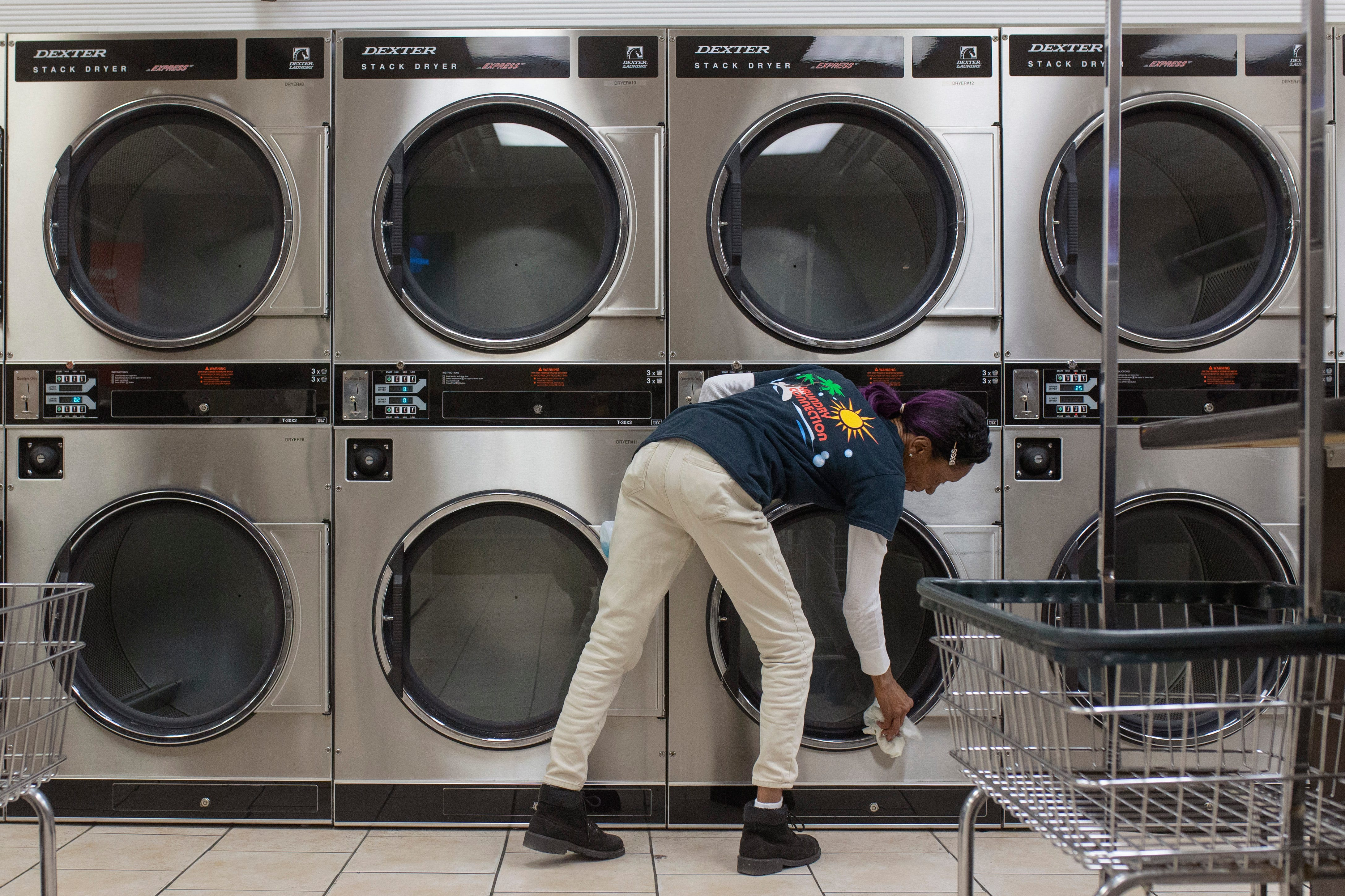 """11:09 PM  """"Miss"""" Margaret Shemwell works on cleaning up the dryers at Laundry Connection on Southgate Avenue just after closing on Jan. 16, 2020. """"I love what I do, because I just love cleaning,"""" Shemwell, who has worked in laundromats for nine years, said."""
