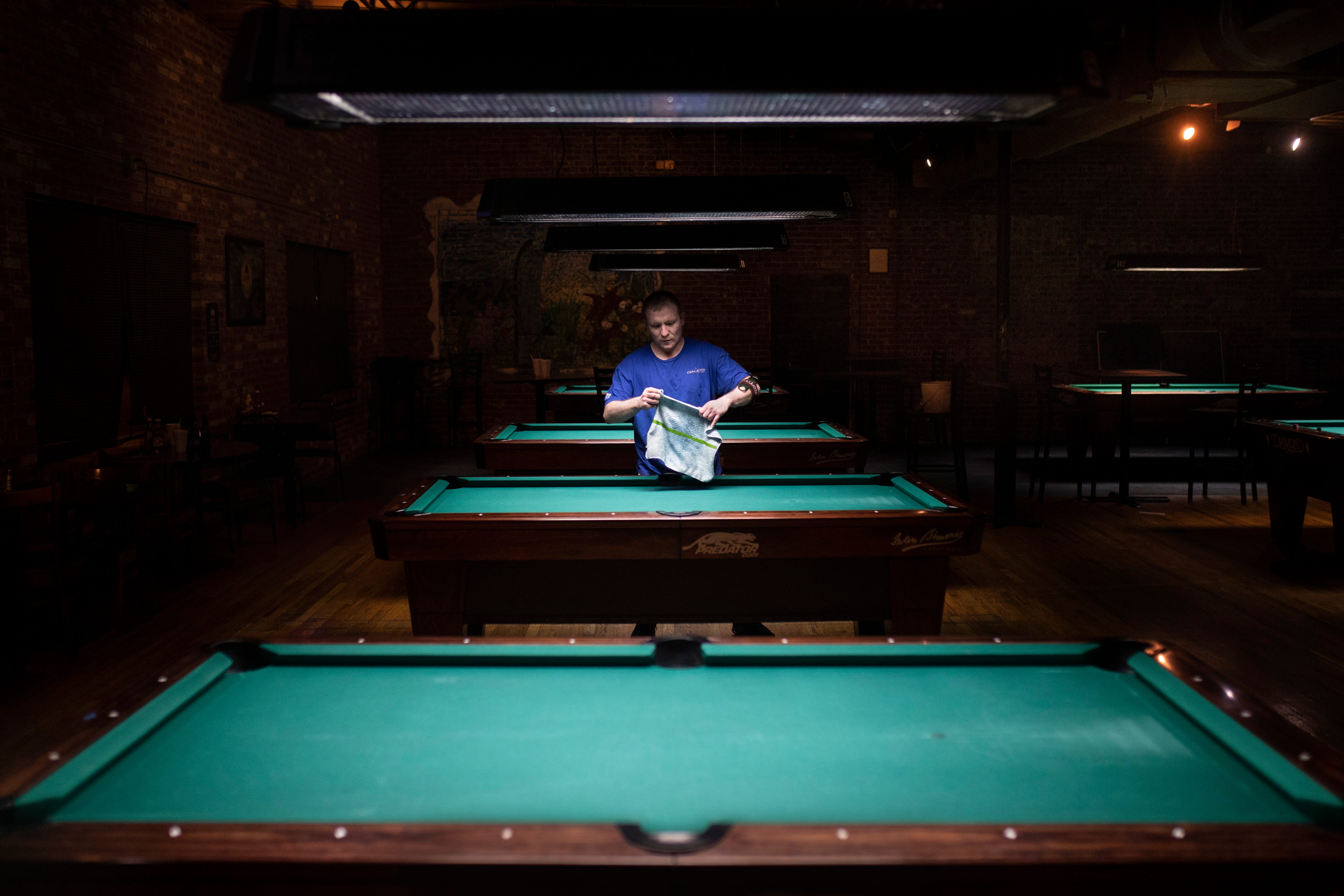 """11:47 PM  Carl Wilkinson cleans the tables at Diamond Pub & Billards on Barret Avenue on Jan. 13, 2020. """"I don't play much pool myself, maybe a couple games a year,"""" Wilkinson said. """"But, if guys shoot and there's chalk still there, it'll affect how the ball moves. We make sure and clean them and have them fresh and ready for every morning."""""""