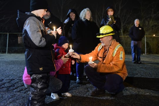 An AK Steel employee helps light candles for children who attended a vigil Tuesday night for Amy Fowler, who was severely burned Friday night.