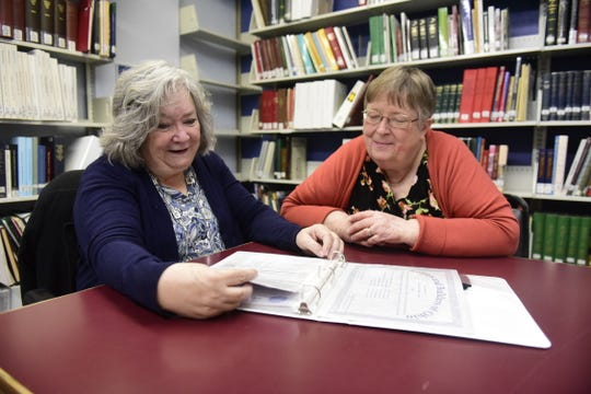 Christina Yetzer Drain, left, and Kathy Webb look over genealogical records in the basement of Marvin Memorial Library in Shelby.