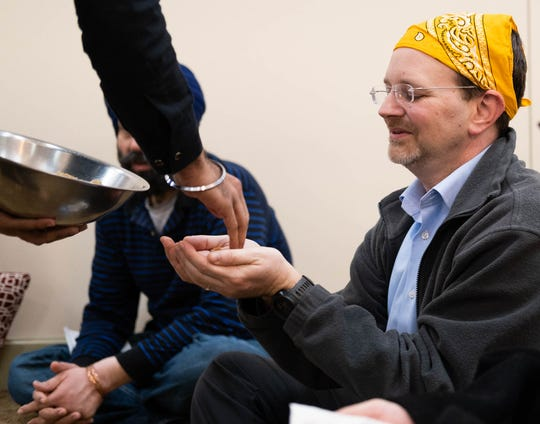 Jason Caplan recieves the Karah Prasad, a sweet delicacy offered at the end of worship, Sunday, Jan. 19, 2020, in Cordova, Tenn.