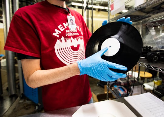 Memphis Record Pressing employee, Evans Bush, checks a pressed record at a vinyl plant in Bartlett, Tenn. on Wednesday, Jan. 28, 2020.