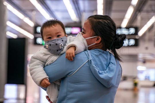 A woman carries a baby wearing a protective mask as they exit the arrival hall at Hong Kong High Speed Rail Station on  in Hong Kong, China.