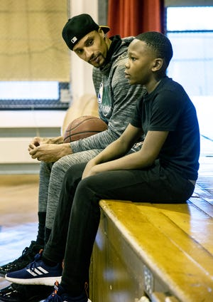 George Hill of the Milwaukee Bucks talks with a student at Clarke Street School earlier this year.
