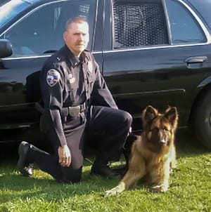 Lt. Dave Huesemann of the Germantown Police Department is sitting with his K9 police dog, Rambo. Rambo died Jan. 27.
