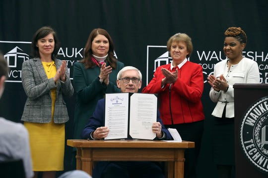 Wisconsin Gov. Tony Evers signs an executive order creating a task force on student debt at Waukesha County Technical College Wednesday. Watching from behind are Lara  Suthererlin, administrator of Division of Trade and Consumer Protection; Kathy Blumenfeld, secretary of the state Department of Financial Institutions; Connie Hutchison, executive secretary of the Higher Educational Aids Board and Maricha Harris, an Alverno College graduate.