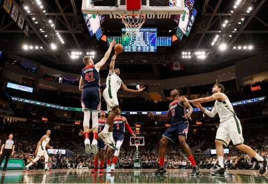 Milwaukee Bucks forward Khris Middleton (22) dunks against Washington Wizards forward Davis Bertans (42) during the fourth quarter at Fiserv Forum.