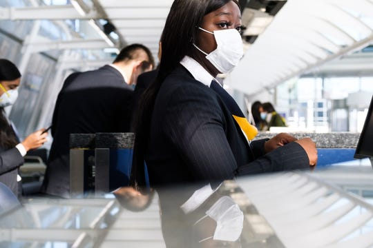 A woman wearing a medical mask checks in passengers at a China Eastern desk at John F. Kennedy International Airport in New York.