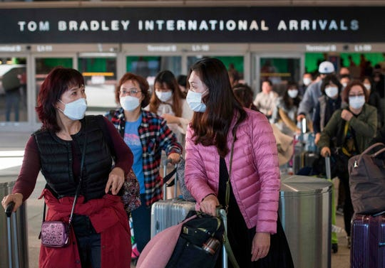 Passengers wear masks to protect against the spread of the coronavirus as they arrive on a flight from Asia at Los Angeles International Airport.