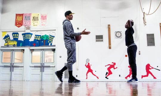 George Hill greets a student at Clarke Street School before beginning a game of one-on-one basketball. Hill has become a mentor at the school.