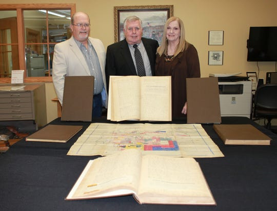 Reference librarian and historian Vincent Anderson (left), Wayne Camp (center) and Carolyn Camp (right) are seen with the historic Baxter County records and maps the Camps recently donated to the Donald W. Reynolds Library.