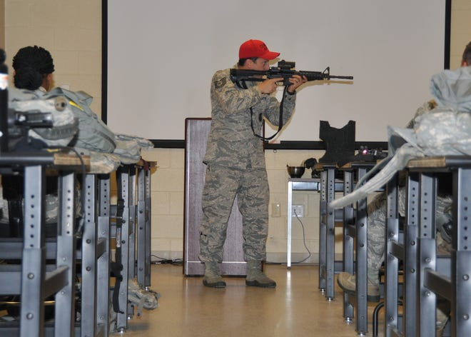 Technical Sgt. James Kuehne, 908th Security Forces Squadron Combat Arms instructor, demonstrates to his class how to properly wield an M4 carbine Nov. 2, 2019, in a classroom at Maxwell AFB, Alabama. Before the Airmen can fire on the range, they have be taught the basic fundamentals, page by page, from Air Force Instruction 36-2654.
