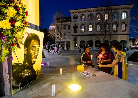 Earnestine Woods, from left, Michelle Browder and John Witt, chat as artists gather to mourn and remember NBA great Kobe Bryant in downtown Montgomery, Ala., on Tuesday evening January 28, 2020.