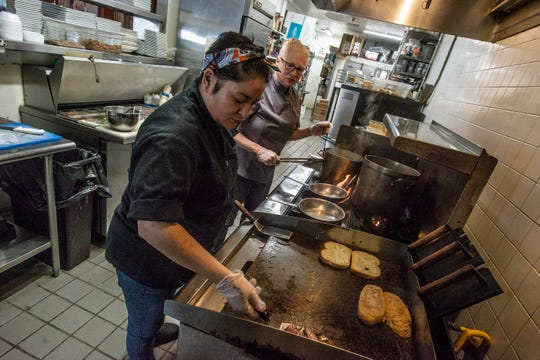 Cork and Cleaver executive chef Renee Merritt, right, and sous-chef Marie Bradley prepare orders in their kitchen.