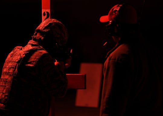 From left, a 908th Security Forces Squadron defender and Technical Sgt. James Kuehne, 908th SFS Combat Arms instructor, oversees an airman shooting an M4 carbine with night vision optics Nov. 2, 2019, in the firing bay at Maxwell AFB, Alabama. Defenders are trained for day, nigh and all types of weather situations so that they can defend in any situation.