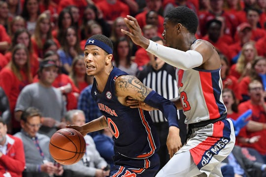 Auburn guard Samir Doughty (10) drives the ball past Mississippi guard Bryce Williams (13) during the first half of an NCAA college basketball game in Oxford, Miss., Tuesday, Jan. 28, 2020. (AP Photo/Thomas Graning)