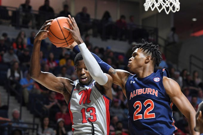 Mississippi guard Bryce Williams (13) rebounds the ball past Auburn guard Allen Flanigan (22) during the first half of an NCAA college basketball game in Oxford, Miss., Tuesday, Jan. 28, 2020. (AP Photo/Thomas Graning)