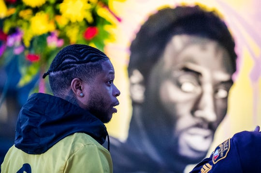 Lazarius Boswell talks about his painting of Kobe Bryant, background, as artists gather to mourn and remember the NBA great in downtown Montgomery, Ala., on Tuesday evening January 28, 2020.