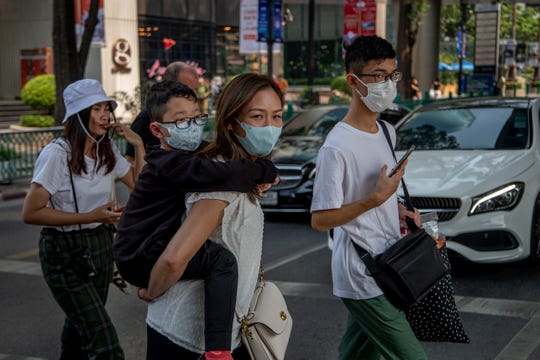 A Chinese family wearing face masks walks in a pedestrian crossing in Bangkok, Thailand, on Wednesday. The coronavirus outbreak, centered in the Chinese city of Wuhan, has killed more than 100 people and sickened thousands.