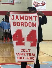 Jamont Gordon shows off the banner signifying his Glencliff No. 44 basketball jersey has been retired.