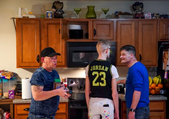 Harry Mercer, left, grabs ingredients for fried pickles while his son Isaac, 13, and husband Joe, right, prepare mashed potatoes in Clarksville, Tenn.