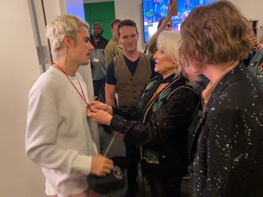 Tanya Tucker gives Justin Bieber a cross necklace backstage at 'Ellen,' as Brandi Carlile (far right) looks on.