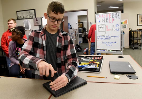 Lakewood High School student Logan Sims takes apart a Chromebook while working in the school's technology center.
